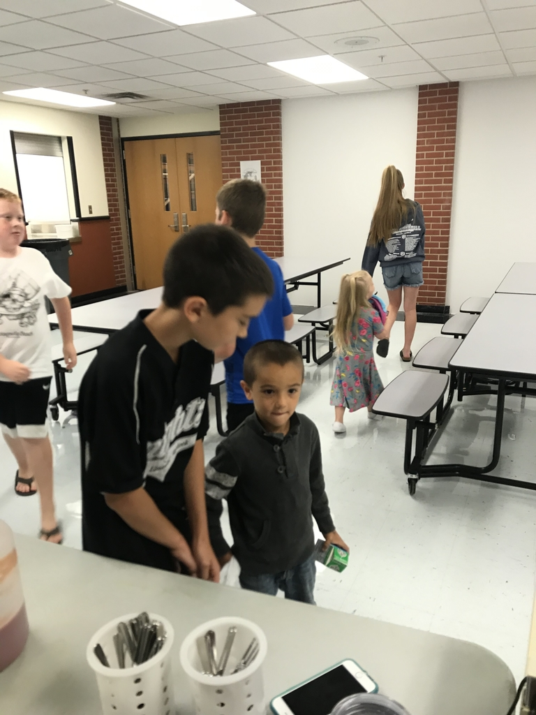 6th grade helps preschool with lunch.